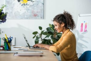 Black woman side profile sitting at desk with hands on laptop keyboard