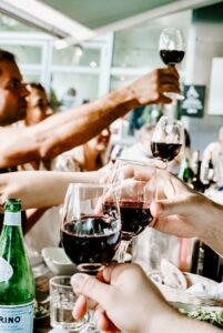 many hands clinking wine glasses together