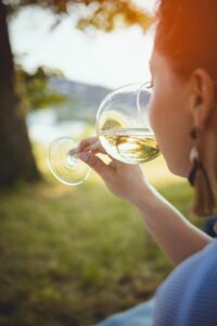 Woman drinking wine green grass sunny day